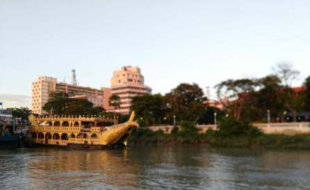 A tour cruise parked at the river bank.
